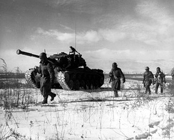 A column of the US 1st Marine Division move through Chinese lines during their breakout from the Chosin Reservoir.
