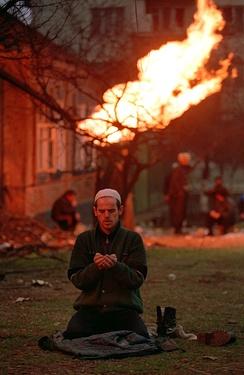Чеченец молится в Грозном, январь 1995г. На заднем плане горит перебитая осколками газовая труба.