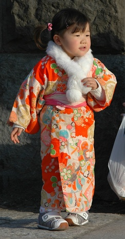 A little girl wearing kimono. A simple soft obi is tied around the waist.