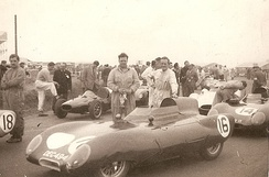"Silverstone Grand Prix, ""Formula Two"" Race, July 1956. Cliff Allison, driver of Lotus Eleven car no.16 leaning on car. He finished fourth. Graham Hill, driver of Lotus Eleven no.18 standing on left. Senior mechanic John Crosthwaite holding cloth"