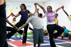 "Michelle Obama joins children for a yoga class during a ""Let's Move!"" after school activities event."