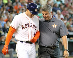 Athletic trainer Nate Lucero (right) evaluates Houston Astros baseball player George Springer after Springer was hit by a pitch in 2014
