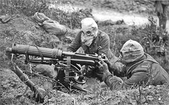 British Vickers machine gun in action near Ovillers during the Battle of the Somme in 1916. The crew are wearing gas masks.
