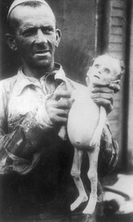 Man showing corpse of a starved infant in the Warsaw ghetto, 1941