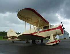 A 1937 Waco VKS-7 cabin-class biplane with its pairs of quadruple ailerons linked by an external vertical connector to simplify its aileron control system. The ailerons on each side thus move either up or down together.