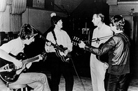 The Beatles working in the studio with their producer George Martin, circa 1965