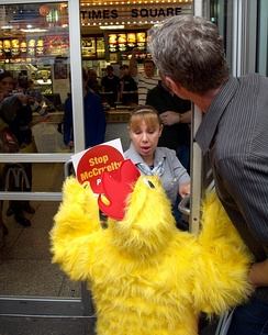 A PETA activist dressed as a chicken confronts the manager of the Times Square McDonald's over the company's animal welfare standards.