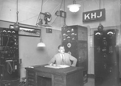 Radio engineer Ernest G. Underwood sitting at desk of his KHJ broadcasting station in Inglewood, 1927