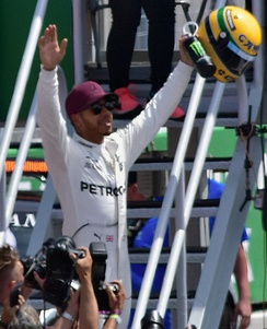 Photo of Lewis Hamilton wearing a red cap and silver overalls holding his arms aloft with a yellow helmet in his left hand