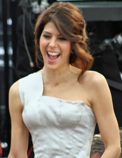 A photo of a brown-haired woman wearing a white dress