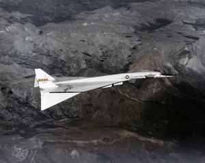 White delta-wing aircraft overflying mountains. The front of the fuselage features canard wings, and the wing tips are dropped.