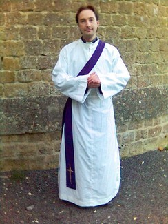 An Anglican priest vested as a deacon with an alb and a purple stole over his left shoulder