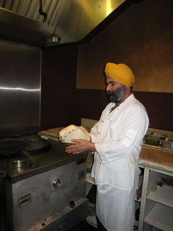 Chef preparing naan to be cooked in a tandoor.