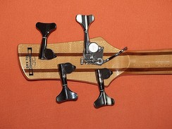 A bass guitar headstock with detuner set to D position