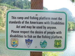 The ADA sets standards for construction of accessible public facilities. Shown is a sign indicating an accessible fishing platform at Drano Lake, Washington.