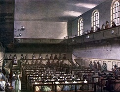 Conservative Friends worshipping in London in 1809. Friends are in traditional plain dress. At the front of the meeting house, the Recorded Ministers sit on a raised ministers' gallery facing the rest of the meeting, with the elders sitting on the bench in front of them, also facing the meeting. Men and women are segregated, but both are able to minister.