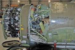 A P-47 engine with the cowling removed. Uncompressed air enters through an intake under the engine and is carried to the turbosupercharger behind the pilot via the silver duct at the bottom. The olive-green pipe returns the compressed air to the engine[5]