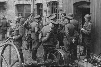 NARA copy #3, IPN copy #3Discussing the evacuation of the factoryGuard on the left is Josef Blösche. Herman Brauer helm repair shop at Nalewki 28-38. 24 April 1943
