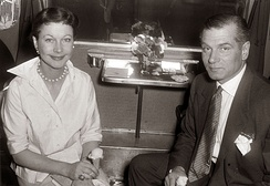 woman and man seated and looking towards camera