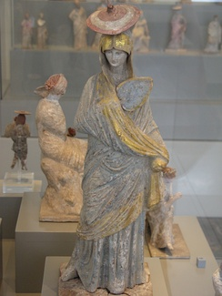 Ancient Greek statue of a woman with blue and gilt garment, fan and sun hat, from Tanagra, 325–300 BC