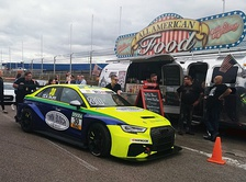 An Audi RS3 LMS TCR in the ADAC TCR Germany Touring Car Championship paddock