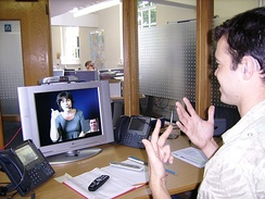 A deaf or hard-of-hearing person uses a Video Relay Service at his workplace to communicate with a hearing person in London (2007)