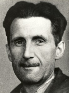 Photograph of the head and shoulders of a middle-aged man, with black hair and a slim moustache.