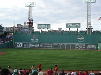 The Green Monster in 2006, showing the manual scoreboard and Green Monster seating, and more recent additions, including charity advertisements along the top, billboards above the Green Monster seating, and the American League East standings.