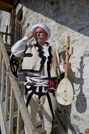 An lahuta player wearing traditional Albanian clothing.