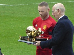 Rooney receiving an award for becoming Manchester United's record goalscorer from previous record holder Sir Bobby Charlton in January 2017