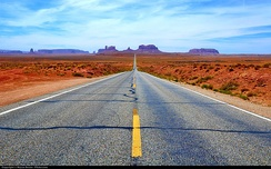 The West, as the most recent part of the United States, is often known for broad highways and freeways and open space. Pictured is a road in Utah to Monument Valley.