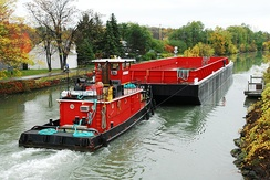 Towboat Herbert P. Brake of New York pushes a new barge east on the Erie Canal in Fairport, New York, United States