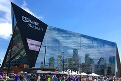 "Blue sky, large angular modern building with reflective surface (Minneapolis downtown visible in reflection). Sign on protruding end says ""u.s. bank stadium."" Crowd of people and vendor tents just visible in foreground"