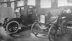 An EV and an antique car on display at a 1912 auto show