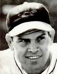 A headshot of a smiling man in a dark baseball cap with a bird on the front.
