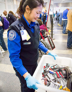 TSA officer carrying a bin of prohibited items that passengers have surrendered.