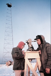 U.S. National Geodetic Survey technicians observing with a 0.2 arcsecond (≈ 0.001 mrad or 1 µrad) resolution Wild T3 theodolite mounted on an observing stand. Photo was taken during an Arctic field party (c. 1950).