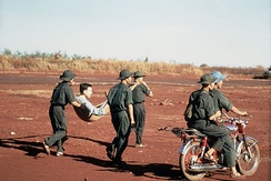 Việt Cộng soldiers carry an injured American POW to a prisoner swap in 1973. The VC uniform was a floppy jungle hat, rubber sandals, and green fatigues without rank or insignia.[78]