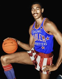 Black man kneeling on one knee with a basketball resting on the other and his hand atop the basketball. He is wearing a red, white and blue Harlem Globetrotters uniform.