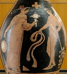 "Woman holding a mirror and a tambourine facing a winged genie with a ribbon and a branch with leaves. Ancient Greek red-figure oinochoe, ca. 320 BC, from Magna Graecia. (Notice the coloured decorative woven stripes hanging on the tambourine, which can still be seen today on ""tamburello"", the tambourine of Southern Italy.)"