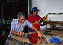Artisan Alfonso Santiago Leyva and his son working with tin sheets.