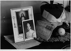 A homemade planter and a doily beside a service portrait, a prayer, and a letter home. One of the few ways to earn permission to leave the camps was to enter military service.