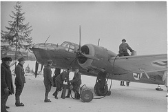 A Finnish bomber plane is being refueled by hand by six servicemen at an air base on a frozen lake.