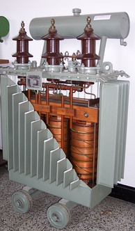 Cutaway view of liquid-immersed transformer. The conservator (reservoir) at top provides liquid-to-atmosphere isolation as coolant level and temperature changes. The walls and fins provide required heat dissipation.