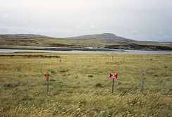 Although some minefields have been cleared, a substantial number of them still exist in the islands, such as this one at Port William on East Falkland.