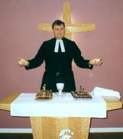 A minister, dressed in a cassock with bands, presides over a service of Holy Communion