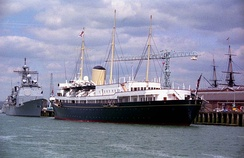 Her Majesty's Yacht Britannia is docked in Portsmouth Harbour for the 50th anniversary of the D-Day Landings in 1994. More modern Royal Navy ships are docked in behind her, and the masts of the HMS Victory can be seen in the far background.