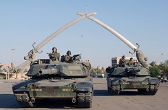 "M1A1 Abrams pose for a photo under the ""Hands of Victory"" in Ceremony Square, Baghdad, Iraq."