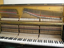 The mechanism and strings in upright pianos are perpendicular to the keys. The cover for the strings is removed for this photo.