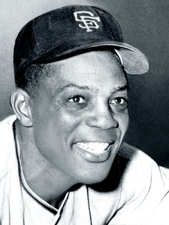 Black-and-white photo of Willie Mays, smiling in a San Francisco Giants hat